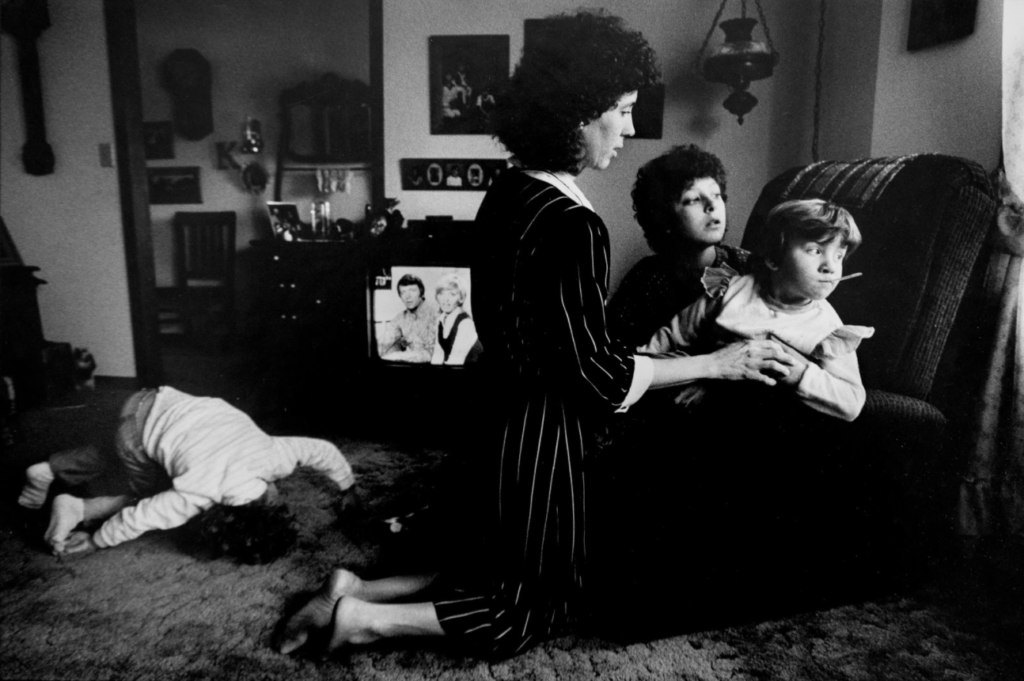 """Carol Keusch checks the temperature of daughter Sandy, one of eight children adopted by Carol and husband David of Vincennes, Indiana. At left, restless daughter Amanda watches """"The Brady Bunch"""" on TV. The family's story covered six pages in the Feb. 8, 1986 edition of The Herald. Photo by Steve Mellon."""
