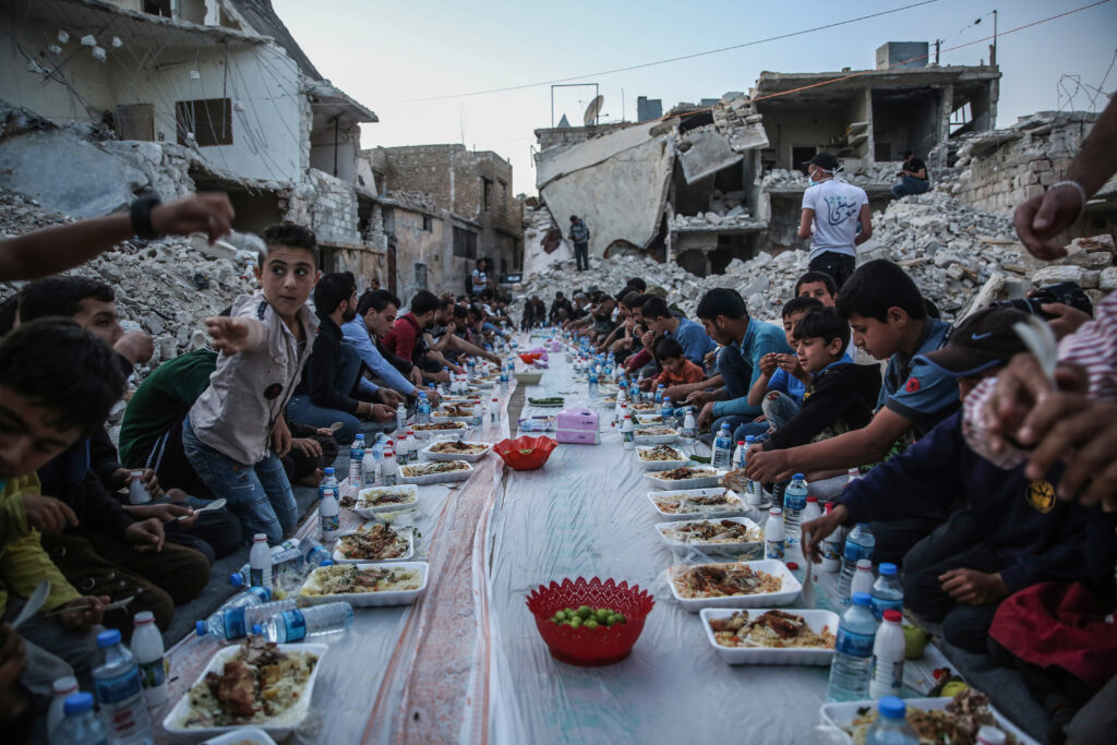 Residents of a Syrian destroyed neighborhood have an Iftar (breaking fast) meal together in Al Atarib town, during the Muslim's holy fasting month of Ramadan. A group of volunteers prepared a mass Iftar for the displaced residents of a neighborhood that was completely destroyed during the military operations in the countryside of Aleppo province.
