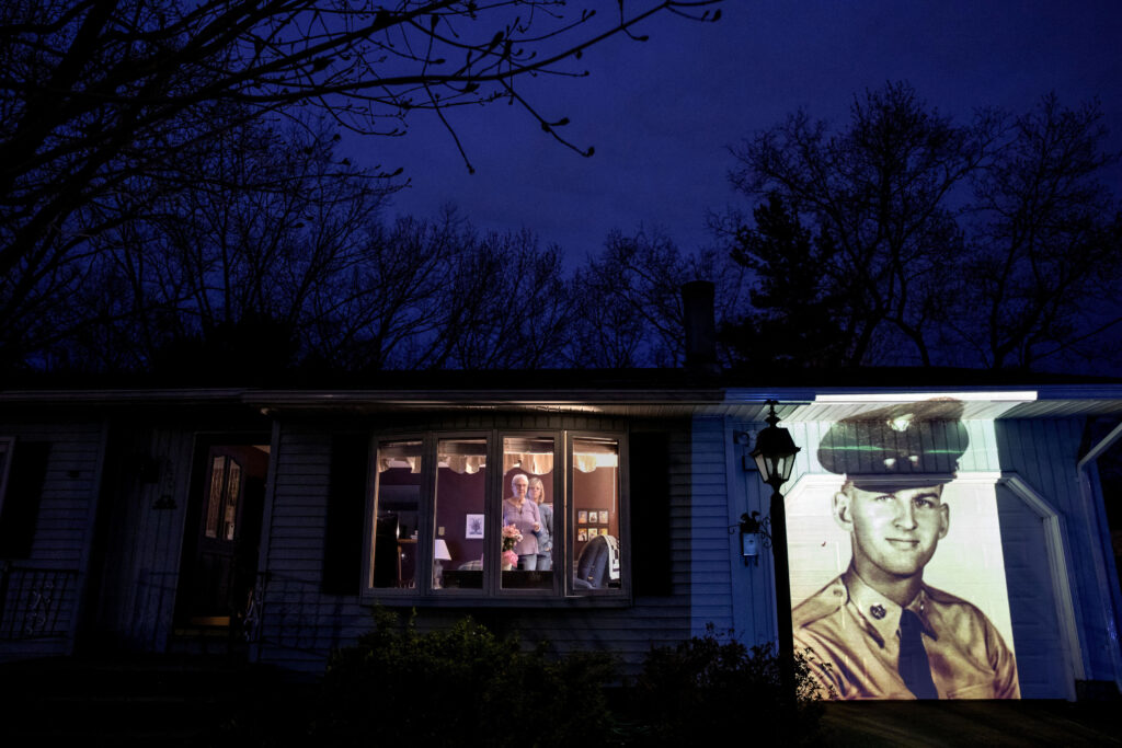 """An image of veteran Francis Foley is projected onto the home of his wife, Dale Foley, left, as she looks out a window with their daughter, Keri Rutherford, in Chicopee, Mass., Wednesday, April 29, 2020. Foley, a U.S. Army veteran and resident of the Soldier's Home in Holyoke, Mass., died from the COVID-19 virus at the age of 84. Foley never learned to read music but could play any song by ear. He loved a cup of coffee and something sweet from Dunkin' Donuts. He kept the nurses at the home laughing. He was fiercely protective of his family. Ask his family about the man they lost, and the words flow easily about the card-carrying union carpenter, Army veteran, devoted husband of 54 years and father of four. """"He was strong. He was funny. He was engaging. He was ornery. He was feisty,"""" his daughter, Keri, says. """"He was still full of life. And then within days, he's gone."""""""