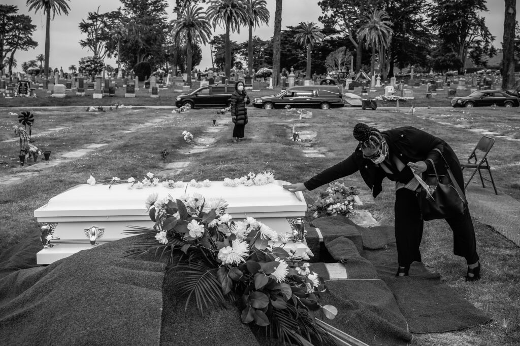 Debra Holloway prays over her mother Tessie HenryÍs casket before saying goodbye to her after Covid-19 at the age of 83 is buried on Wednesday, April 8, 2020, in Colma, California.