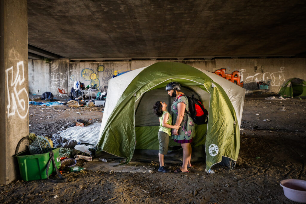(L-r) Homeless child Theo Schrager, 7, holds on to his mom Leah Naomi GonzalesÕ hand as he cries out ÒPuppies, I want puppies.Ó as they look for puppies at their friends tent under the Gilman Street underpass in Berkeley, California, on Friday, June 12, 2020. They spent the afternoon looking for their friend Elf who has two new puppies. Theo loves dogs and desperately wants one. ÒMama, I want one and I want one now.Ó Theo declared. She answered, Ò Theo, I have way too much to take care of. ThereÕs just no way we can have a dog in that hotel room.Ó
