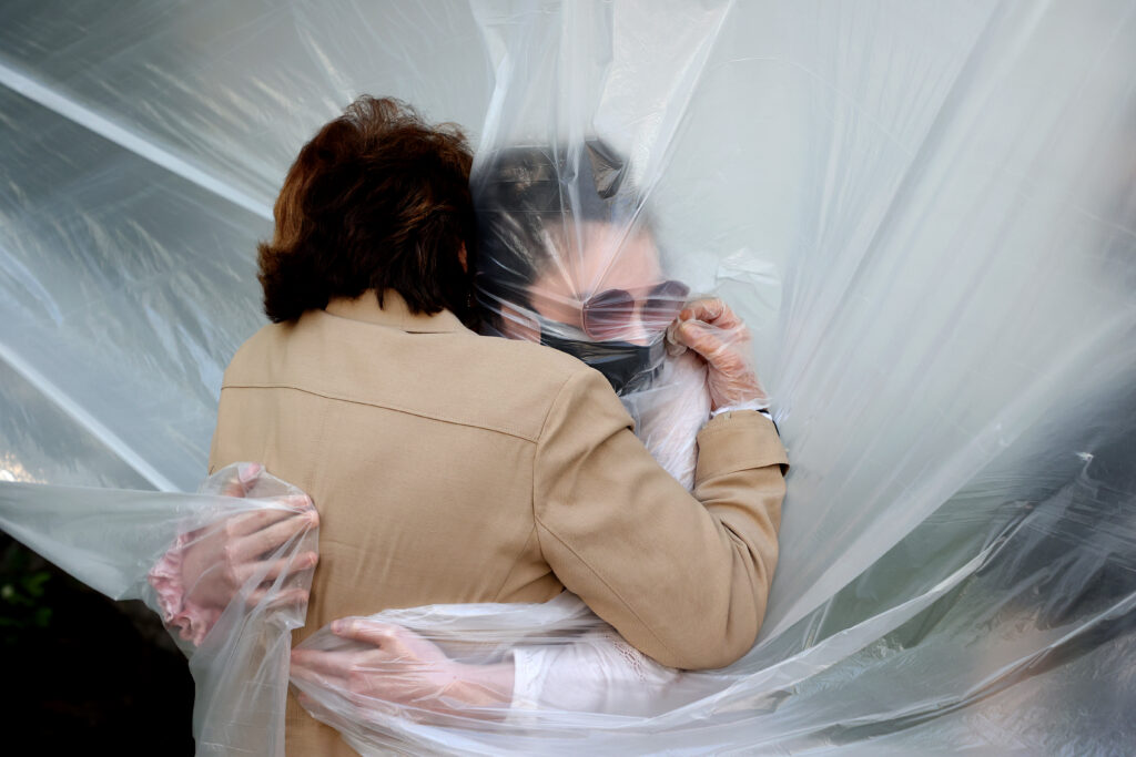 WANTAGH, NEW YORK - MAY 24: Olivia Grant (R) hugs her grandmother, Mary Grace Sileo through a plastic drop cloth hung up on a homemade clothes line during Memorial Day Weekend on May 24, 2020 in Wantagh, New York. It is the first time they have had contact of any kind since the coronavirus COVID-19 pandemic lockdown started in late February. (Photo by Al Bello/Getty Images)